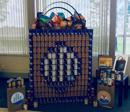 "The ""Golden Can Awards"" and ""With Flying Colors"" Award went to River City Construction for the ""Weigh-A-Ton"" category using 920 plus cans and boxes of food, and for their use of packaging and label colors for their ""Baggin' It Up"" grocery bag demonstrating ""Just imagine what this bag ""CAN"" do for our community!""."